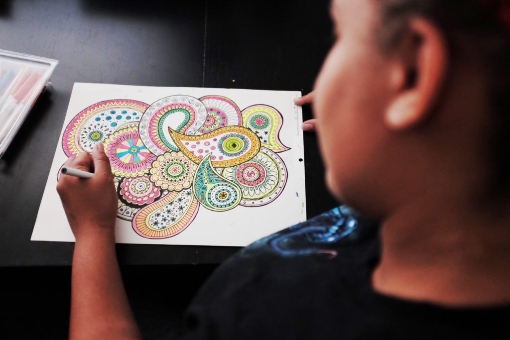 Image of a youth at Wind Youth Services coloring a mandala